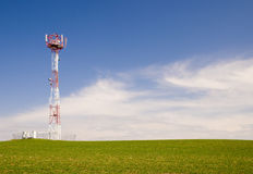 Telecommunication tower. On the green field with blue sky Royalty Free Stock Image