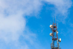 Telecommunication tower antenna with blue sky and cloud background. Stock Image
