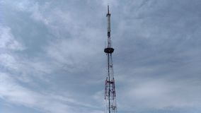 Telecommunication tower blue clouds on blue sky background