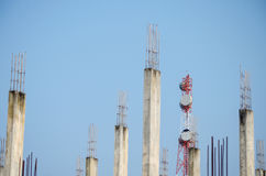 Telecommunication tower and blurred old abandoned building. In front of blue sky Royalty Free Stock Image