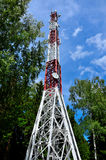 Telecommunication tower with cellular and satellite antennas against the blue sky and forest Royalty Free Stock Photos