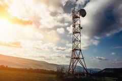 Telecommunication tower with dish and mobile antenna on mountains at sunset sky background stock photo