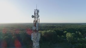 Telecommunication tower, drone view of worker servicing cellular antenna stock footage