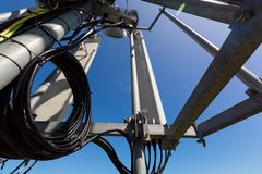 Telecommunication tower or mast with microwave, radio panel antennas, outdoor remote radio units, power cables, coaxial. Cables, optic fibers are on the top royalty free stock images