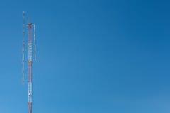 Telecommunication tower mast TV and radio antenna on blue sky Royalty Free Stock Photography