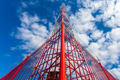 Telecommunication tower with panel antennas and radio antennas and satellite dishes for mobile communications 2G, 3G, 4G, 5G. With red fence around tower royalty free stock photos