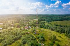 Telecommunication tower with radio antennas and satellite dishes is installed on the rural on the green field with gras. S, bushes and trees. Concept of harmless stock image