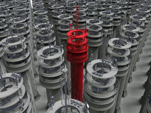 Telecommunication tower - target in crowd. 3D render illustration of multiple telecommunication towers. One tower is colored in red indicating the target in the Stock Image