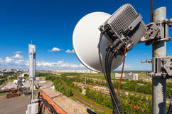 Telecommunication tower with wireless communications systems are including microwave, panel antennas, fiber, optic and power cabl Royalty Free Stock Photos