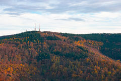 Telecommunication towers on the summit of the hill covered with colorful fall forest Royalty Free Stock Images