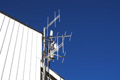 Telecommunication towers with TV antennas and satellite dish on clear blue sky Royalty Free Stock Photos