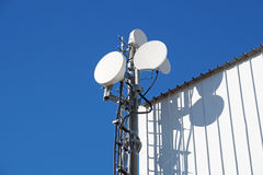 Telecommunication towers with TV antennas and satellite dish on clear blue sky Stock Image