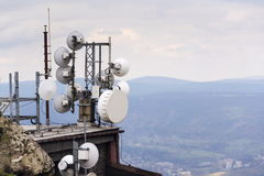 Telecommunication transmitters and aerials with city background Stock Images
