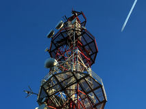 Telecommunications. Tower an airplane passing by Royalty Free Stock Images