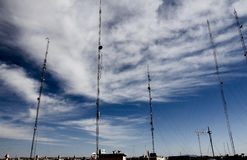 Telecommunications antennas on a cloudy blue sky Stock Photography