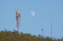 Telecommunications Antennas in the Forest. With Clear Blue Sky and the Moon Royalty Free Stock Photography