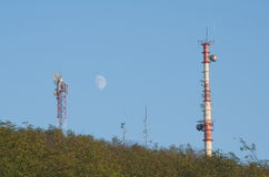 Telecommunications Antennas in the Forest. With Clear Blue Sky and the Moon Royalty Free Stock Photos