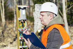 Telecommunications fitter near Communication Cables enclosure. At outdoor Stock Photography