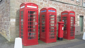 Telecommunications at Fort George. Three original red phone boxes with one modified to send and receive email and a post box for slow mail, stone wall in fort royalty free stock photo
