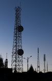 Telecommunications landscape. Landscape showing broadcasting antenas at sunset with an intense blue to grey gradient stock photo