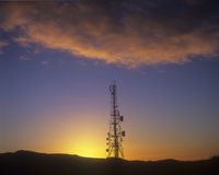 Telecommunications Mast. On top of hill at sunset Stock Image
