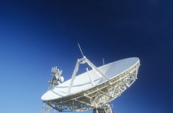 Telecommunications satellite dish and communications towers Royalty Free Stock Image