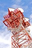 Telecommunications Tower. A red and white telecommunications tower against a bright cloudy sky Stock Photography