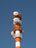 Telecommunications tower. Orange and white coloured telecommunications tower with clear blue sky in the background royalty free stock images