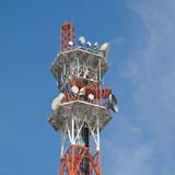 Telecommunications tower. Orange and white coloured telecommunications tower with blue sky and thin white clouds in the background stock photos