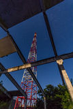Telecommunications tower of abandoned structures against night stars stock image