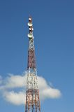 Telecommunications tower. Against blue sky Stock Photos
