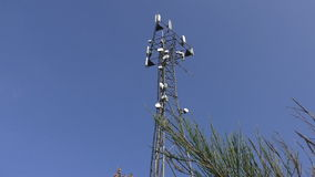 Telecommunications tower against blue sky stock video footage
