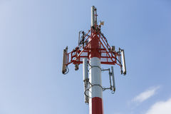 Telecommunications tower. Against blue sky, in red and white Royalty Free Stock Image
