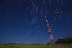 Telecommunications tower in a field and star trail Royalty Free Stock Photography