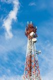 Telecommunications tower with many satellite dish on blue sky cloud background. Royalty Free Stock Image