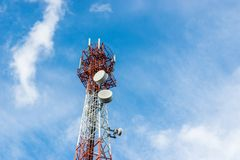 Telecommunications tower with many satellite dish on blue sky cloud background. Stock Image