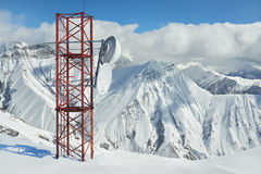 Telecommunications tower in mountains. Telecommunications tower in the mountains in winter on a background of rocks and peaks Stock Photography
