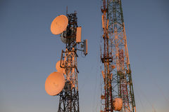 Telecommunications tower at sunrise and blue sky Royalty Free Stock Images