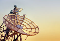 Telecommunications tower at the sunset. Parabolic antennas on a telecommunications tower at the sunset Stock Photography