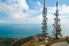 Telecommunications towers. Panorama with two telecommunications towers against sea and sky Royalty Free Stock Photo