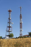 Telecommunications towers. On hilltop under sunlight Royalty Free Stock Image