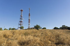 Telecommunications towers. On hilltop under sunlight Royalty Free Stock Images