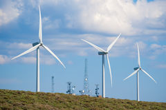 Telecommunications towers and wind turbines Stock Images