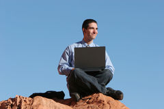 Telecommuting. Young man working on his laptop royalty free stock photos