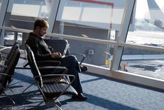 Telecommuting at the airport. Man working on laptop at the airport launge royalty free stock photography