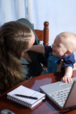 Telecommuting Break. A businesswoman working from home, holding her smiling baby son royalty free stock photography