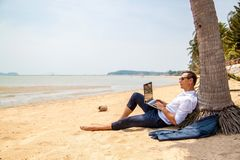 Telecommuting, businessman relaxing on the beach with laptop and palm, freelancer workplace, dream job. Conceptual photo about the journey royalty free stock images