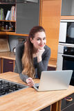 Telecommuting concept - happy young woman thinking and working with laptop. Telecommuting concept - happy beautiful young woman standing, leaning her head on her royalty free stock images