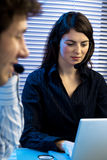 Teleconference. Two young business people sitting at desk, having a teleconference, talking on headset Royalty Free Stock Images
