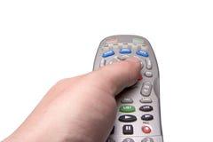 Telecontrol masculino de la televisión de la explotación agrícola de la mano Foto de archivo libre de regalías